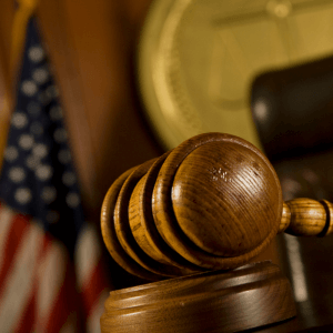 Picture of a gavel in a courtroom with an American flag in the background